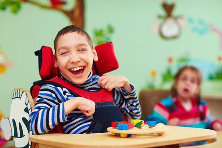 wesoły chłopiec z niepełnosprawnością w centrum rehabilitacji dla dzieci ze specjalnymi potrzebami