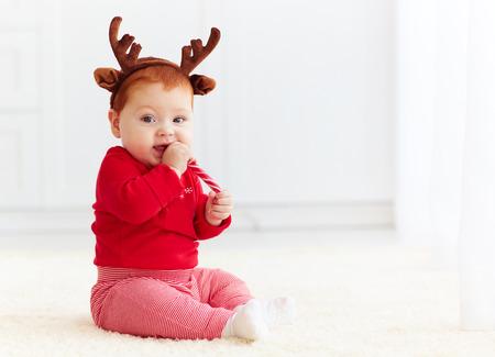 niedliche Rothaarige Baby zu Hause Weihnachten Süßigkeiten essen