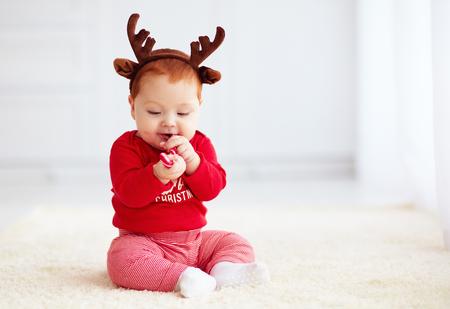 mignon bébé roux mangeant noël bonbons à la maison
