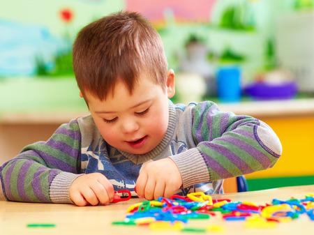 유치원에서 놀고있는 다운 증후군을 가진 귀여운 아이 스톡 콘텐츠