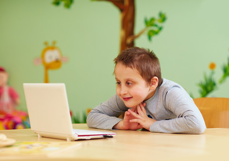 needs: young boy with special needs watching media through the laptop