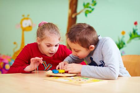 the working day: niños con necesidades especiales a desarrollar su motilidad fina en el centro de rehabilitación guardería Foto de archivo