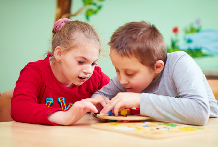 kids with special needs develop their fine motor skills in daycare rehabilitation center Stock Photo