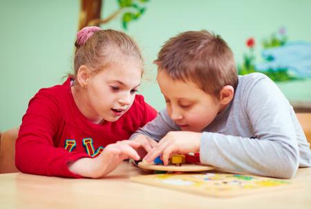 les enfants ayant des besoins particuliers à développer leurs habiletés motrices fines dans le centre de réadaptation de garderie Banque d'images