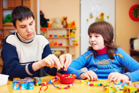 kids with special needs develop their fine motor skills in daycare rehabilitation center Archivio Fotografico