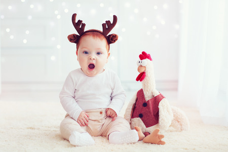 cute yawning baby on christmas background with rooster cock toy Stock Photo