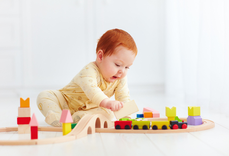 cute ginger baby playing with toy railway road at home