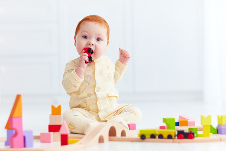 cute ginger baby playing with toy railway road at home. Tasting wagon Stock Photo - 67190726