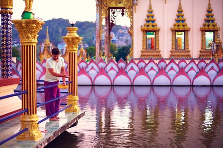 young adult man feeding fishes in beautiful buddhist temple
