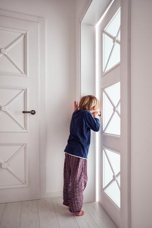 keek: curious young boy looks into the ajar door
