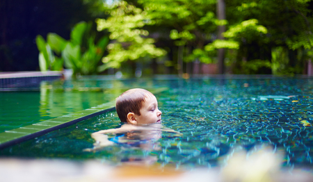 quiet baby: young baby boy ralaxing in pool at quiet peaceful place