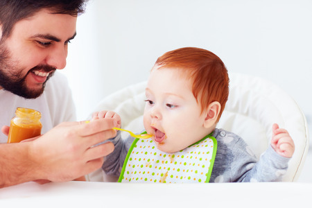happy father feeding cute redhead baby with complementary food Stock Photo