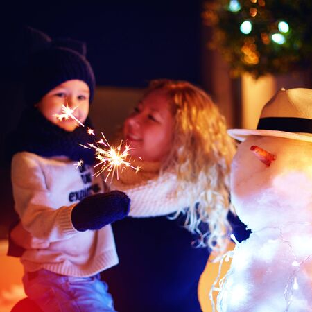 celebrate year: happy mother and son celebrate new year with sparklers and snowman. Focus on sparklers Stock Photo