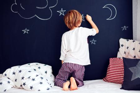 stars night: cute kid in pajamas painting chalkboard wall in his bedroom