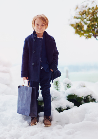fashionable, seven years old boy in coat, holds bag outdoors