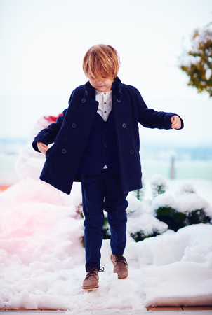 fashionable, seven years old boy in coat outdoors