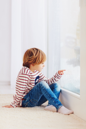 winter blues: handsome young boy sitting on carpet near the window at rainy day