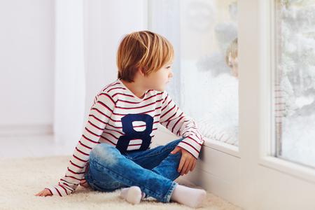 雨の日で、窓際のカーペットの上に座って若い美少年