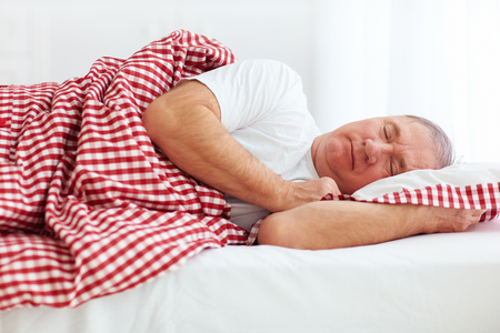 person: calm mature man sleeps in bed