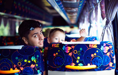 happy father and son traveling on public tourist bus through Malaysia