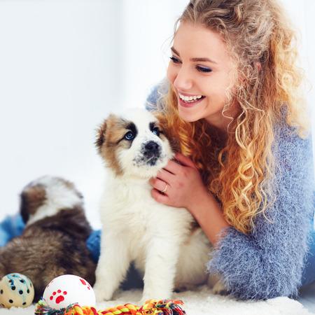 beautiful woman playing with cute caucasian shepherd puppies