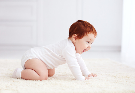 happy, nine months old baby crawling on carpet at home Stock Photo
