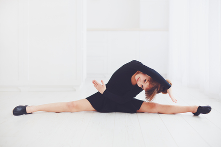 beautiful young girl doing stretching exercises at ballet school Stock Photo