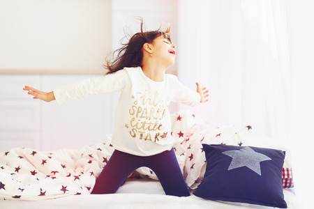 vigorous: happy vigorous young girl wakes up in the morning sun light, singing in bedroom