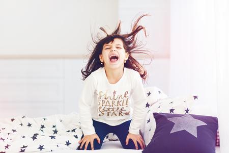 vigorous: vigorous young girl singing in bed in the morning sun light