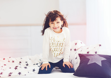 vigorous: happy vigorous young girl wakes up in the morning sun light, cute toothless smile Stock Photo