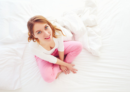 young smiling woman sitting on bed in the morning Фото со стока