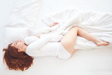 ベッドで安らかに寝ている若い女性のトップ ビュー