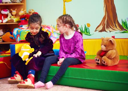 특별한 필요를 가진 아이들을 위해 유치원에서 이야기하고 노는 귀여운 소녀 스톡 콘텐츠