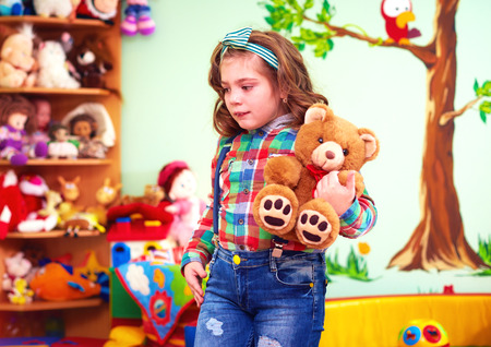 kids toys: cute girl playing with toys in kindergarten for kids with special needs Stock Photo