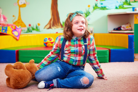 cerebral palsy: cute girl playing in kindergarten for kids with special needs