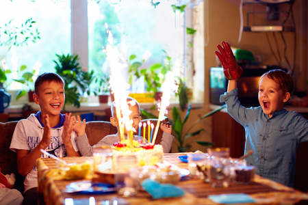 birthday party kids: delighted kids blowing candles on cake, while celebrating a birthday party at home