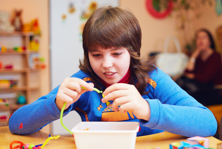 cerebral palsy: happy kid with disability develops fine motor skills at rehabilitation center for kids with special needs