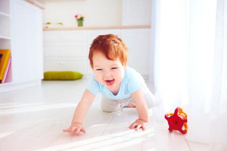 집에서 바닥에 크롤 링하는 귀여운 생강 아기 소년 스톡 콘텐츠