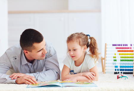 paternal: happy father and daughter spending time together by reading interesting book