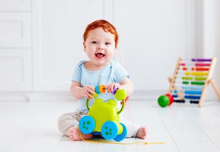 happy infant baby boy playing with toys at home