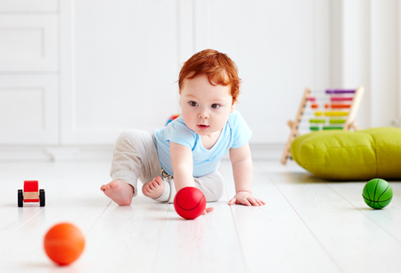 10 month: cute infant baby crawling on the floor at home, playing with colorful balls Stock Photo