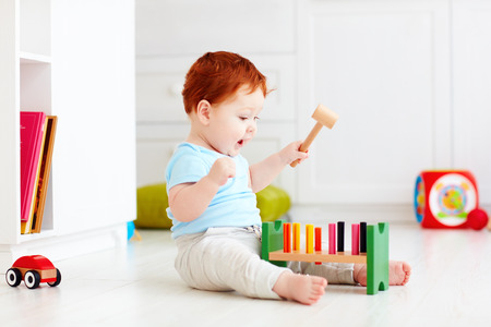 cute infant baby playing with wooden hammer block toy 스톡 콘텐츠