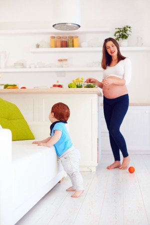 pregnant young mother looks after infant baby at home