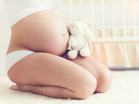 regnant: beautiful belly of pregnant young woman sitting on carpet in nursery room Stock Photo