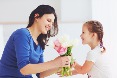 happy daughter giving mother a spring flower bouquet