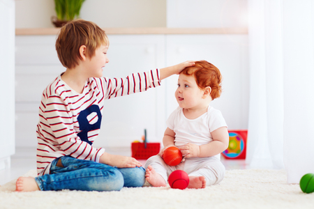 babysit: cheerful senior kid playing with his junior toddler brother at home Stock Photo