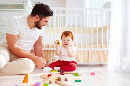 paternal: happy father playing with infant baby boy at sunny nursery room