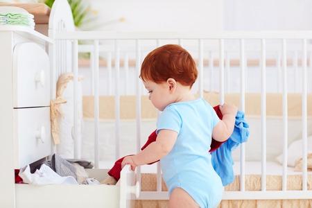 Zabawne dziecko niemowląt wyrzucić ubrania z komody w domu