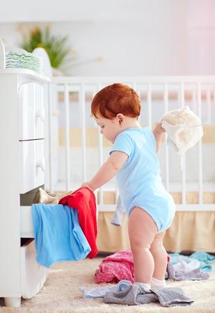 grappige zuigeling baby die kleren uit de dressoir thuis werpt Stockfoto