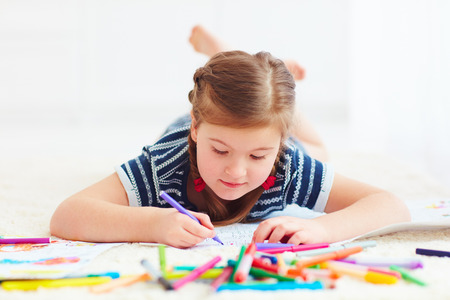 portrait of cute happy girl drawing, while laying on carpet